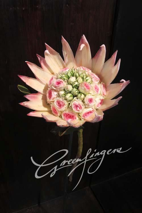 Greenfingers - pink protea petals surrounding pink and white roses