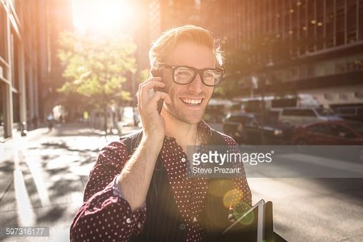 Stock Photo : Happy young businessman strolling city street talking on smartphone, New York, USA