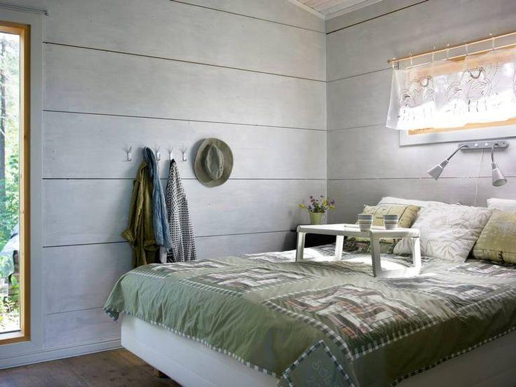 De massive veggene er holdt enkle og rene, med kun knagger med klær som dekor. De naturgrønne fargene i sengeteppe og puter står i fin stil til resten av rommet og skaper en rolig atmosfære.