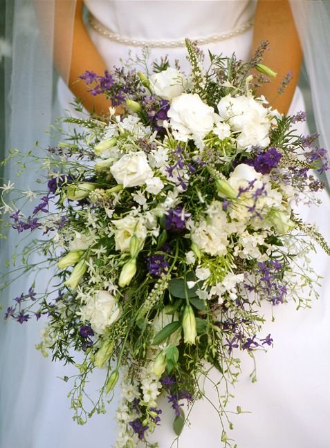 Cascade bouquet of white lisianthus, phlox, ivy, lavender, mignonette, larkspur, veronica, rosemary and summer savory