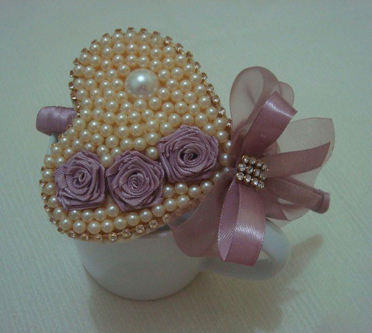 Tiara encapada em fita rosa chá com lindo coração em pérola e laço de fita em organza com detalhes em strass muito charmosa. Então princesa encomende já a sua.