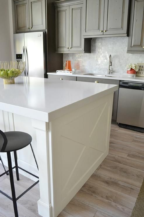 Beautiful kitchen features gray cabinets paired with white quartz countertops and a marble hex tile backsplash.