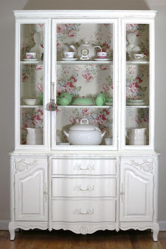 SOLD  This china cabinet is sold , but I can make something similar for you.  -------------------------------If you are not able to pay the full price at once, ask us about payment arrangements------------------  A beautiful vintage French Provincial china cabinet that has been painted a creamy white color with light distressing. On the back wall is a beautiful paper which adds extra character. This piece is a sturdy solid wood construction with a lot of storage. Its a perfect addition to…