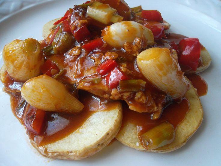Pollo aderezado sobre papas fritas con cebolla cambray y pimiento morron