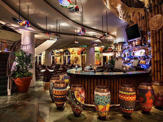 The colorful bar area with bongo drum shaped bar stools at Bongos Cuban Cafe