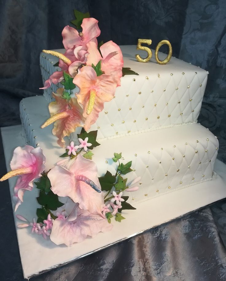 Traditional rich fruit cake covered in marzipan and fondant, sugar paste anthuriums and jasmine blossoms