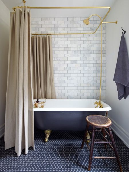 Black marble hex tiles are a hip backdrop for a refurbished clawfoot tub. The small scale of the tiles make the floor in this compact bathroom seem larger. For more ways to incorporate a top trend for
