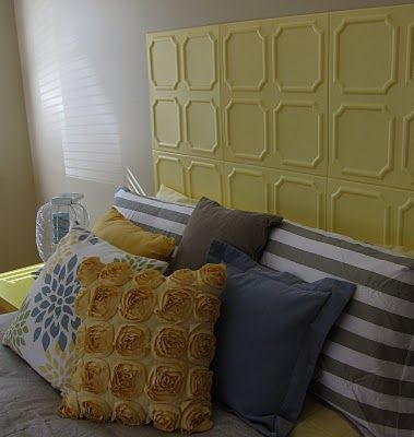 The faux headboard is a DIY project. Styrofoam tiles (intended for the ceiling) for around $20, painted them yellow, and attached them to the wall with sticky adhesive squares.