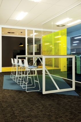 Blue, orange, and yellow, the Roche brand colours, predominate through the workplace meeting rooms and informal break-out spaces.