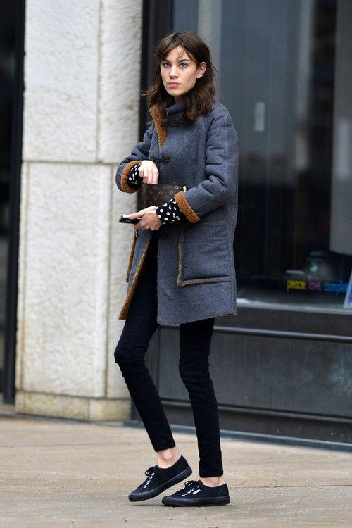Alexa Chung in layers; blue and brown winter coat, black leggings, black  lace up shoes, polka dot shirt.