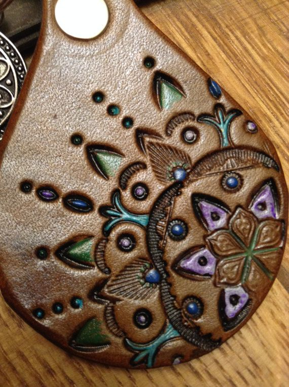 Tooled leather mandala design keychain dyed in medium brown with blue, green, purple, and turquoise accents. Also a silver charm. Please message me if you wish for other colors. Im sold out of the mandala charm with the purple stone and I have not been able to reorder a supply.