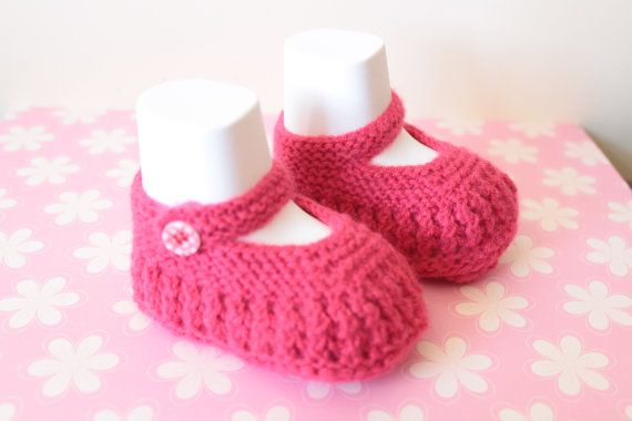 Pretty lacy hand knitted baby booties. These raspberry pink baby booties have been made in a wool mix yarn. These pretty little shoes fasten with a