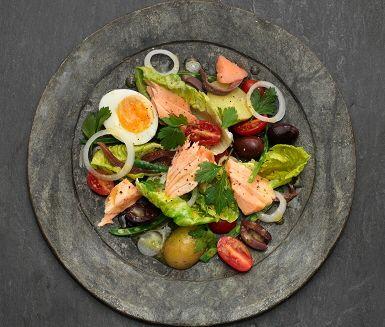 Sallad Nicoise med ugnsbakad lax är en snabb och matig sallad med potatis, haricots verts och ägg. Laxfilén blir saftig på låg temperatur i ugn, och fisken passar bra med salladens salta sardeller och oliver.