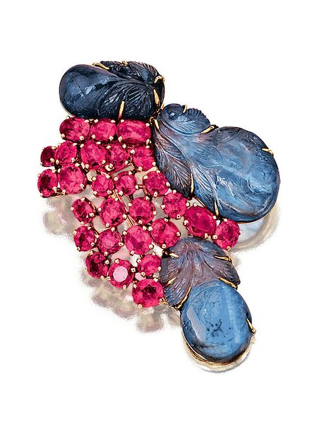 SAPPHIRE AND RUBY BROOCH, SUZANNE BELPERRON, 1950S The brooch of foliate inspiration designed as a stylised bunch of leaves and fruits, set with carved sapphires, circular-cut and oval rubies, mounted in yellow gold, French assay and maker's marks.