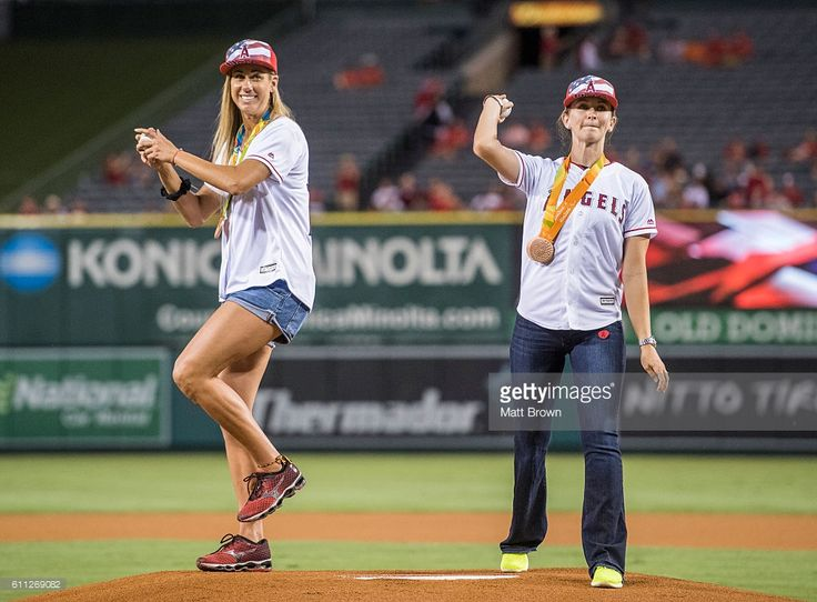Rio 2016 bronze medalists Olympic beach volleyball player April Ross and Paralympic cyclist Samantha Bosco throw ceremonial first pitches before the game against the Oakland Athletics at Angel Stadium of Anaheim on September 26, 2016 in Anaheim, California.