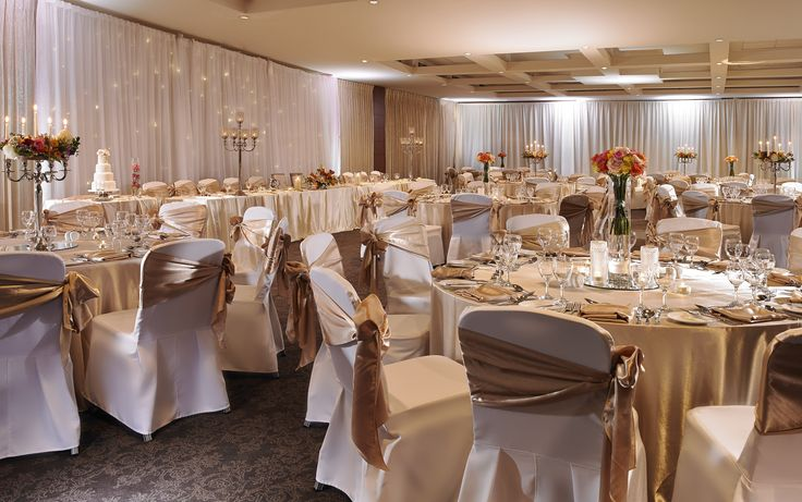 Summer Wedding Setting with summer flower arrangement and champagne table cloth and sash