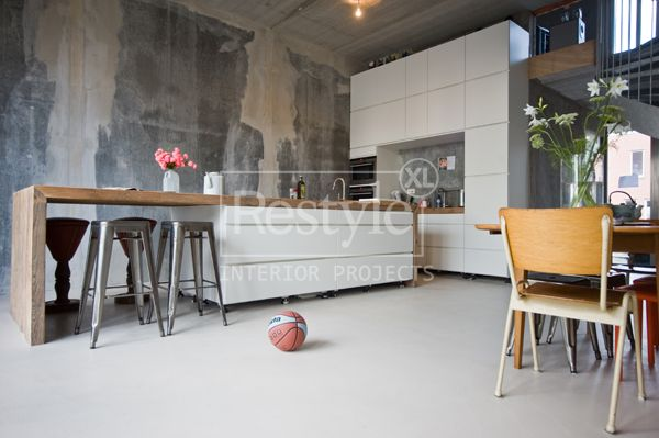 Witte keuken met hout in hoge ruimte.