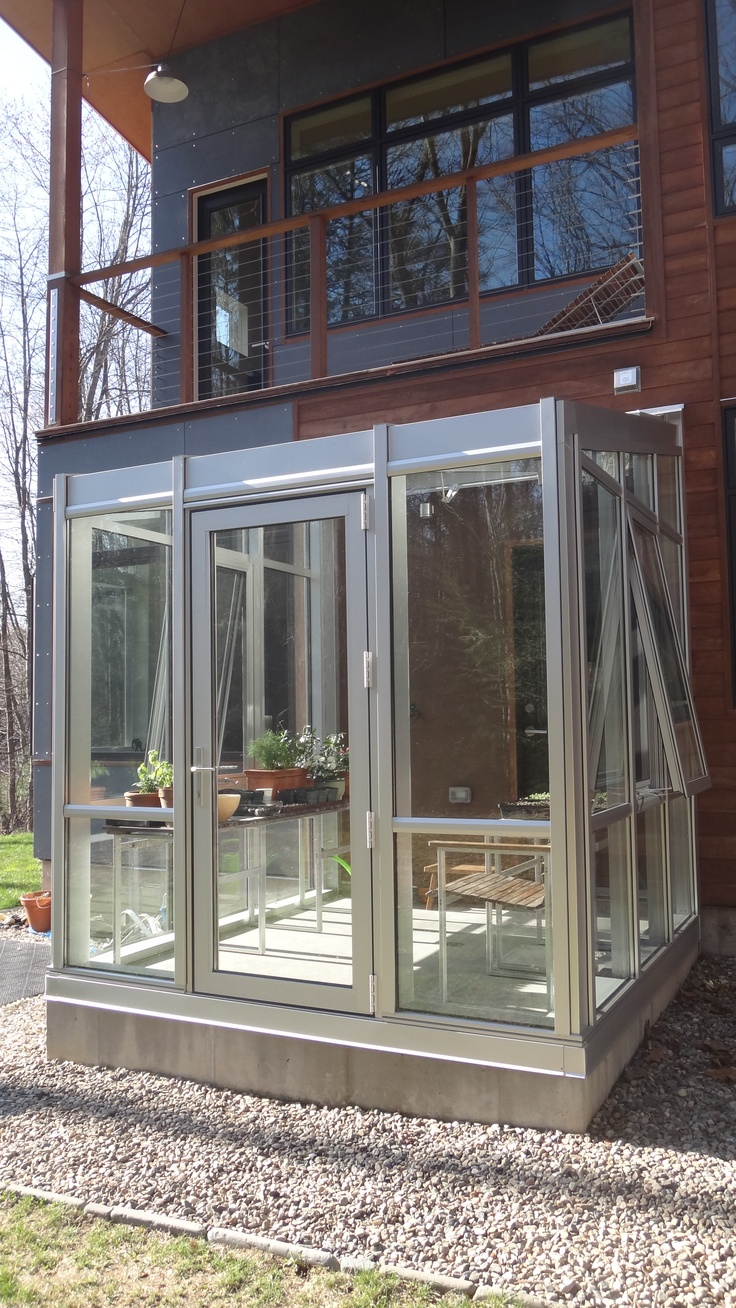 This is a residential hobby greenhouse located on the back of the house. An exterior door allows for easy transportation of potting soil and plants, without entering the house. The silver color adds to the contemporary design.