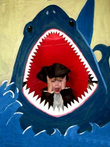 Pirate Party - Paint a shark on a large piece of cardboard. Cut out the mouth, watch those teeth. Tape a red cloth (I used a plastic table cloth). And tada, not only do you have a feed the shark game (throw bean bag in it's mouth) but you also have a great photo prop