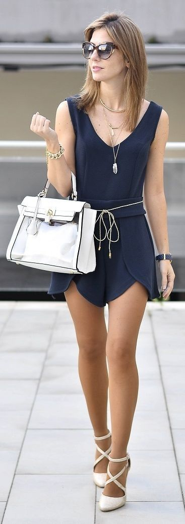 Navy romper and nude heels with large white purse for a summer outfit.  Rompers are an easy throw on and go item that belongs in every closet.  To make this romper more casual you can pair it with gladiator sandals and a jean jacket.
