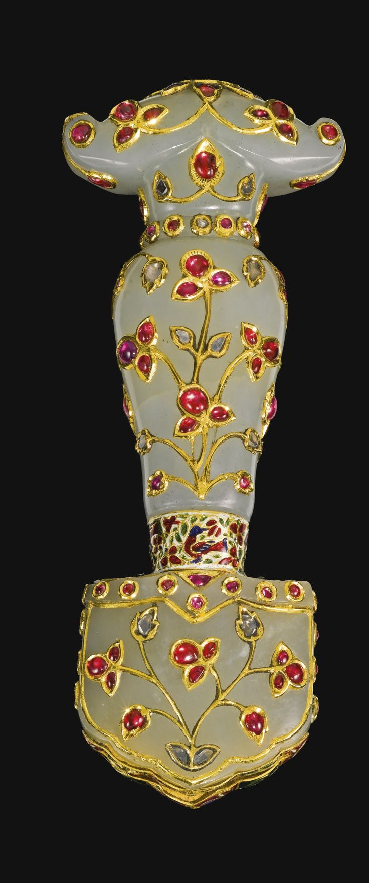 A Mughal gem-set jade hilt with enamelled band, India, 19th century. The carved jade hilt of baluster form, set with foil-backed diamonds, rubies and coloured gemstones designed as floral stems, connected to the lobed jade chape decorated en-suite by a polychrome enamelled band with birds amidst foliage.