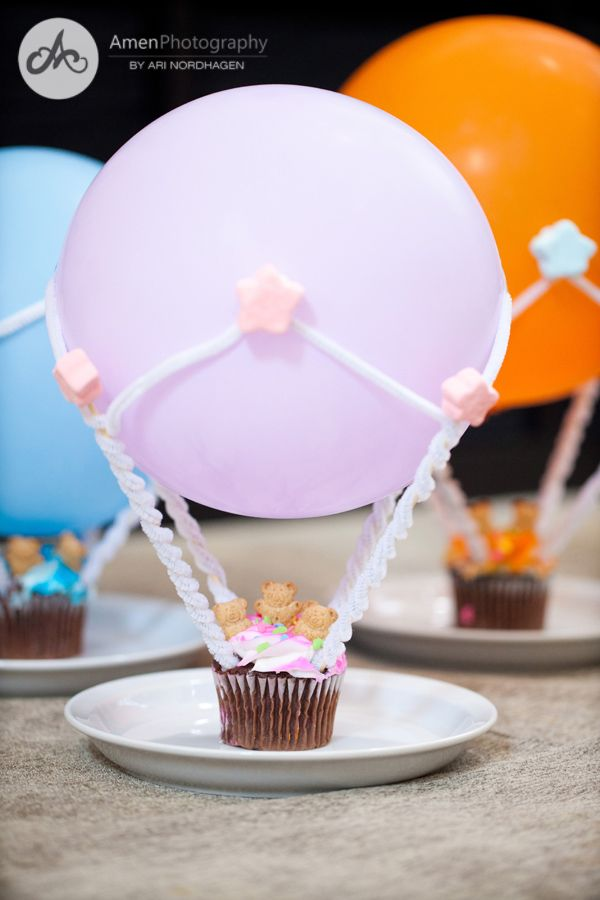 "Hot Air Balloon Cupcakes - Use small bamboo skewers wrapped in white wire brushes (two per skewer), then topped with star shaped marshmallows. The wire brushes were taped to the balloons at the ends where they meet and covered with star-shaped marshmallows ""glued"" with frosting. Passengers are little teddy grahams. @erika"