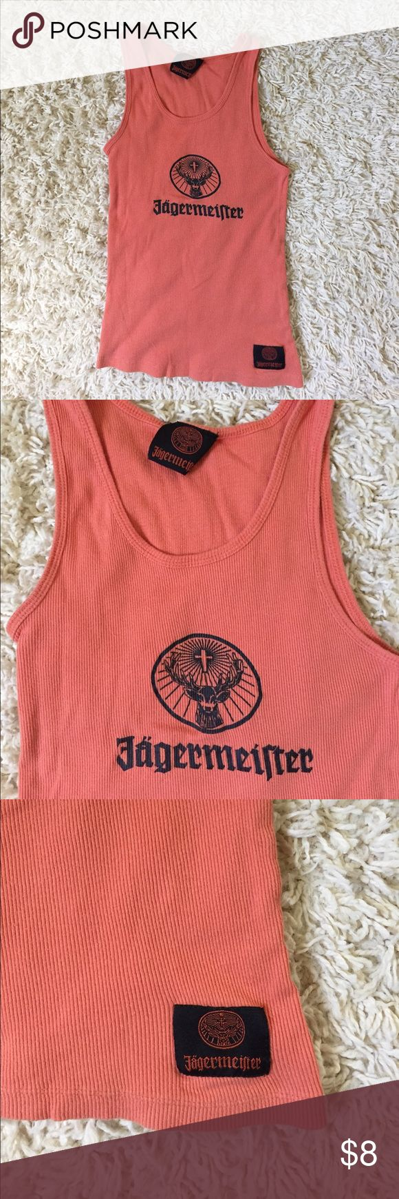 Orange and Black Jagermeister Deer Cross Logo Tank Orange and black wife beater style tank from Jagermeister with their logo on front.                           Tag size size Large but it's honestly a small or xs. There is some minor unraveling at bottom hem on back that you can see in photo. I think this may have been an irregular make because it was tagged incorrectly and the seems don't match up exactly. But would still be a cute summer tank or to wear under leather or jean jacket. Great…