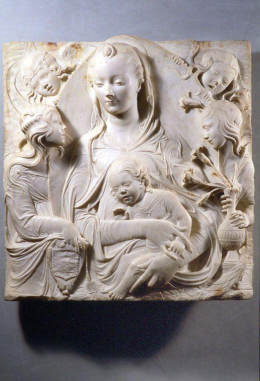 """Agostino di DUCCIO Florence, 1418 - Pérouse, 1481  La Vierge et l'Enfant entourés par quatre anges (""""Madone d'Auvillers"""")  Marbre H. : 0,81 m. ; L. : 0,76 m. ; Pr. : 0,14 m.  Probablement exécuté entre 1464 et 1469 pour Pierre de Médicis, dit """"le Goutteux"""" (1419 - 1469). Donné par la famille Bonnières de Wierre à l'église d'Auvillers (Oise). Louvre"""