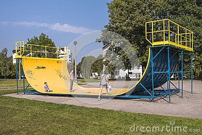 Yellow ramp Skate Park and children playing in the area of Krakow, Nowa Huta. Poland .