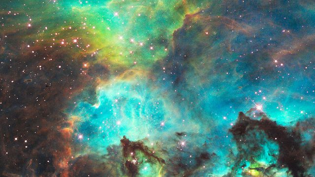 """NGC 2074 Hubble peered into a small portion of the nebula near the star cluster NGC 2074 in this 18th anniversary image. The region is a firestorm of raw stellar creation, perhaps triggered by a nearby supernova explosion. The image reveals dramatic ridges and valleys of dust, serpent-head """"pillars of creation,"""" and gaseous filaments glowing fiercely under ultraviolet radiation. The region is on the edge of a dark molecular cloud that is an incubator for the birth of new stars."""