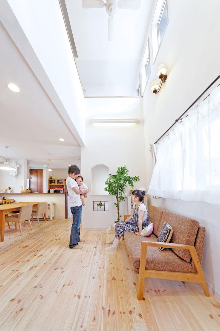 大きな吹抜けで明るく開放的なリビング。珪藻土塗り壁と無垢パイン床材の自然素材が心地いい。