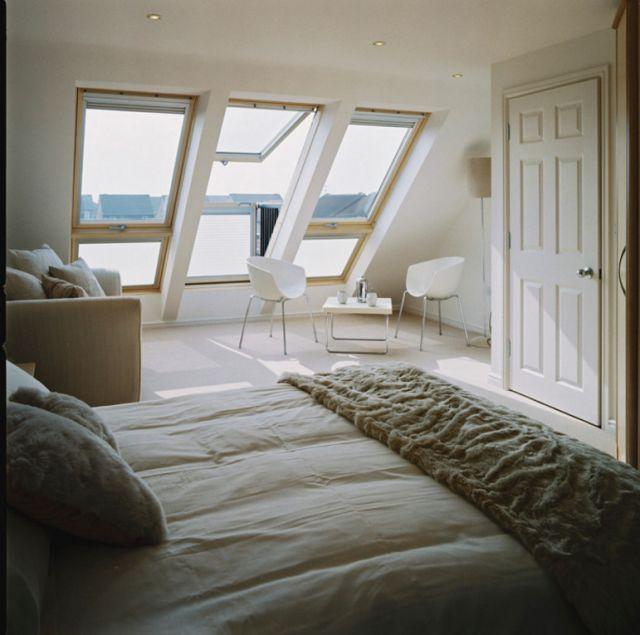 勾配天井に埋め込まれた天窓がバルコニーになるVELUXのCABRIOのあるベッドルーム