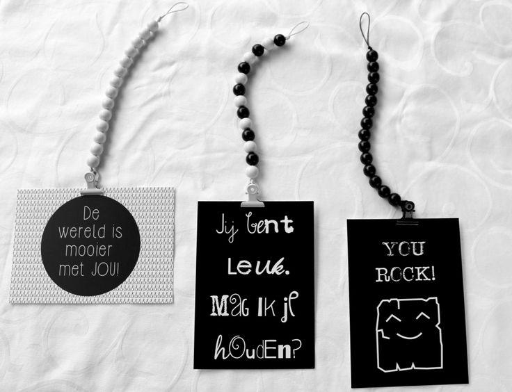 woonkettingen in zwart en wit van houten kralen geregen met een leren koord. Met knijpertjes met snor om decoratie op te hangen zoals kaarten,posters,tekeningen of mini metalen bordjes.