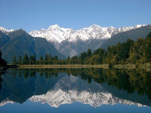 Lake Matheson (aka Mirror Lake), near the Fox Glacier in South Westland, New Zealand, is famous for its reflected views of Aoraki/Mount Cook and Mount Tasman: Lakes Matheson, Mirror Lakes, Foxes Glacier, Aka Mirror, Togo Places, Matheson Mirror, Travel Free, New Zealand, Matheson Aka