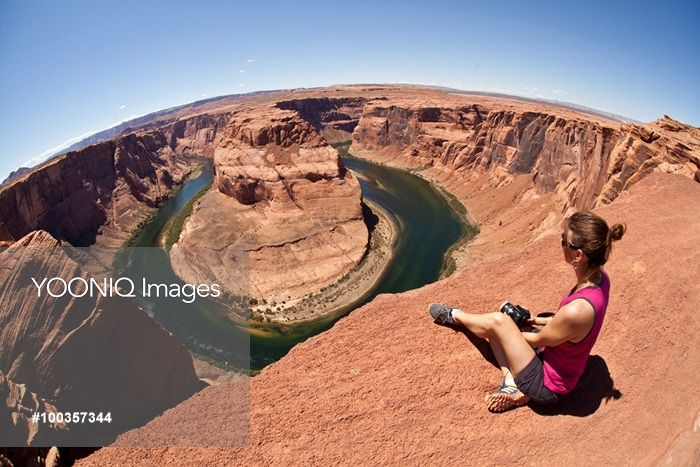 Yooniq images - A woman sits above Horseshoe Bend at the edge of a canyon.