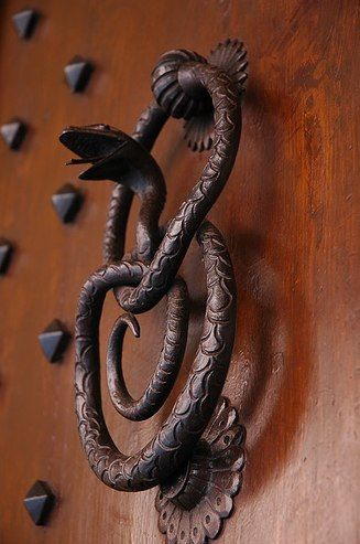 A door knocker in the form of coiled snake about to strike, symbolically protecting against evil.
