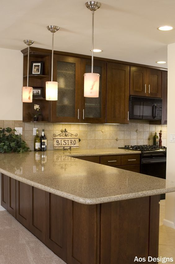 Like the G-shape with seating and hanging lights. Darker cabinets up to ceiling with lighter countertop.