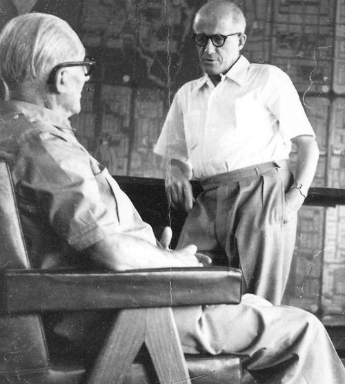 Le Corbusier (seated) and Pierre Jeanneret in front of map of Chandigarh.