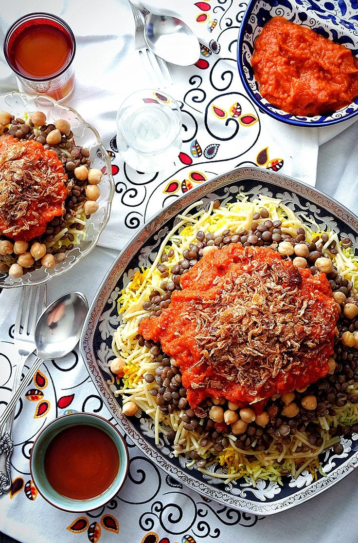 Koshari: Egypt dish of rice, lentils and macaroni with cumin, served with crispy onions and a sharp tomato sauce.