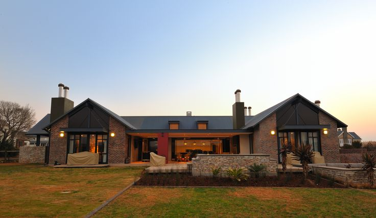 House Uys in Pretoria, South Africa. This is a single storey home built in a farming estate and located with views over the neighboring golf course, enjoying the best of both worlds. A steel I-beam and wood structure, reminiscent of an elongated spine, frames the western facade from the street, while leading the eye to the front door. Completed 2010 by Mathews and Associates Architects. Photo courtesy of Wenzel Kotze.