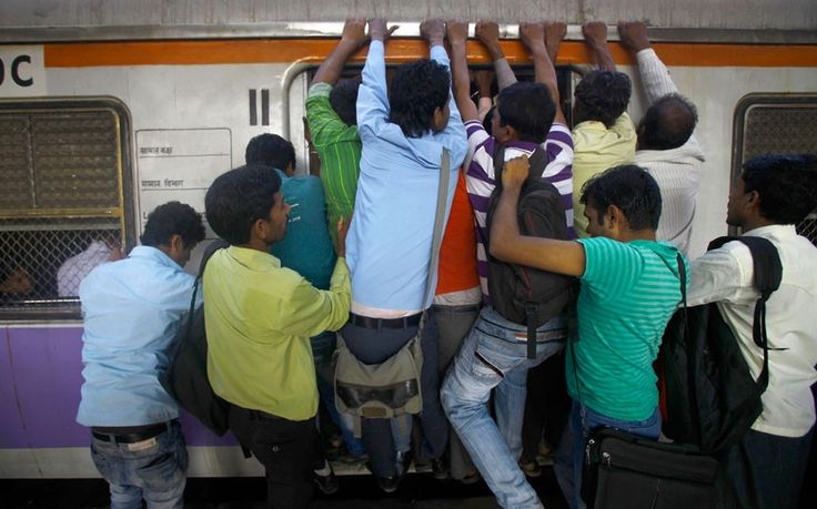 Commuters try to board an overcrowded train in Mumbai Picture: Rafiq Maqbool/AP