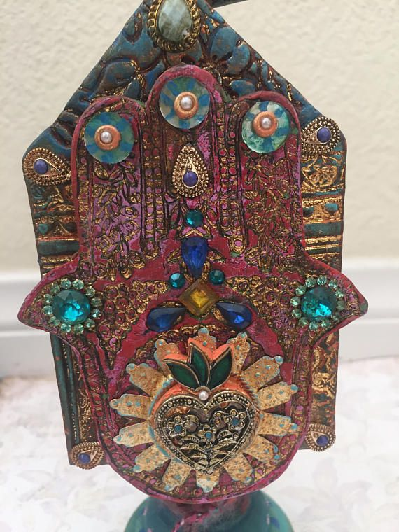 This small bird house-shaped totem features a Hamsa created out of layered polymer clay. The Hamsa symbol has been used in many different ancient cultures. Generally it is a symbol of protection and is thought to ward off the evil eye. Both sides of this wood structure have hand images as