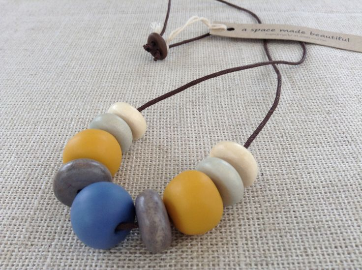 9 bead mustard and mid-blue necklace on cord.