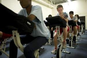 Nik Osborne and the rest of his peers pedal on their FitDesks as they read in Jennifer Payne's lifetime wellness class at Glencliff High School.  These desks with pedals underneath them cost $300 each.