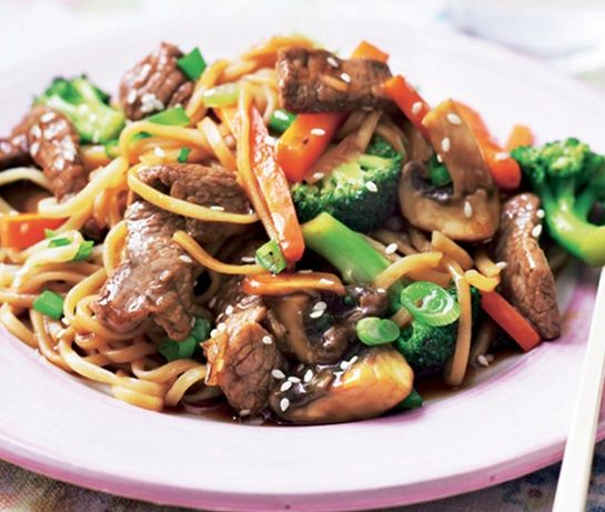 plate with rump steak, broccoli, onion, carrots, mushrooms and noodles in a sauce