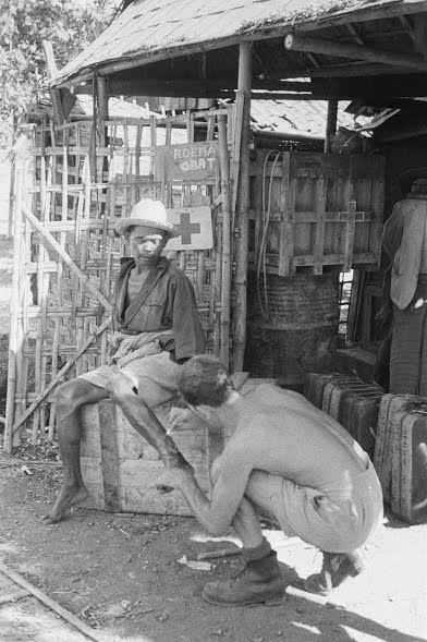 Soerabaja. Een verpleegkundige van een Rode Kruispost behandelt het been van een man. Op het bordje bij de deur staat geschreven 'Roema obat' 1946 (Collectie nationaal archief)