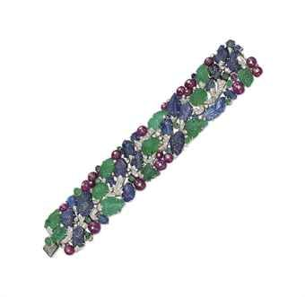 AN ART DECO DIAMOND AND MULTI-GEM 'TUTTI-FRUTTI' BRACELET, BY CARTIER The pavé-set diamond branch with carved sapphire and emerald leaves, cabochon sapphire and emerald collets, ruby bead berries and enamel detail, 1930s.