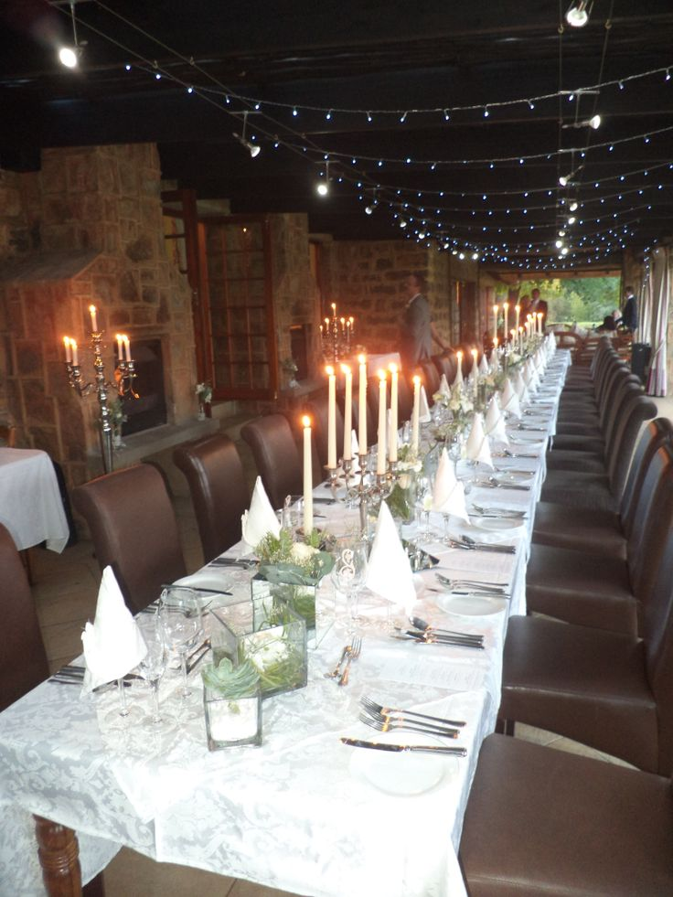 The dinner table with a multitude small, varied flower arrangements, mirror underplates & mirror vases to reflect the lights, lots & lots of candles and romantic fairy lights.