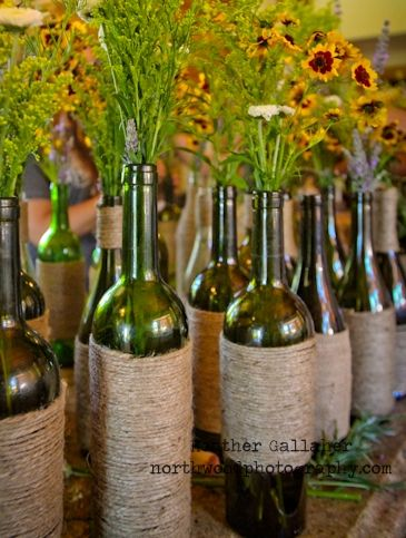DIY wine-bottle centerpieces. Wrap rustic twine around wide part of bottle, then decorate with various wild flowers.