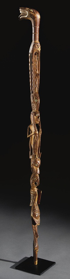 A NORTHWEST COAST WOOD STAFF, PROBALY TLINGIT    composed of carved wood and abalone shell, depicting a shark, surmounted in turn by an eagle, wolf, a human and other totemic creatures.   Height 35 in.